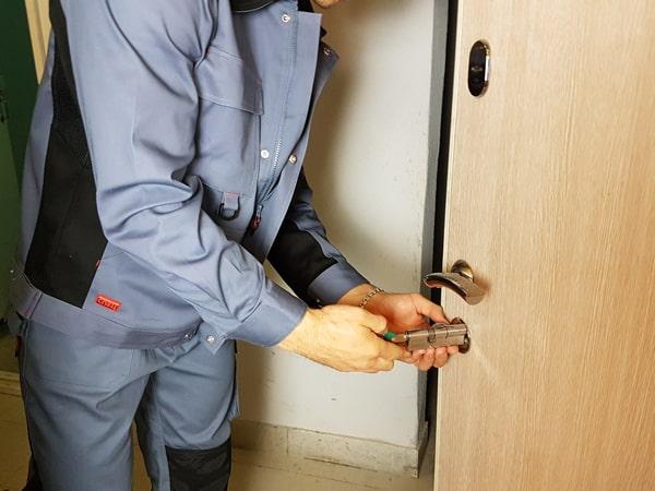 Мастер меняет замок на двери